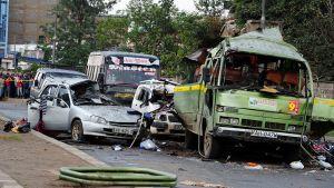 Kranaatti-iskussa vaurioitunut bussi ja autoja kadulla Nairobissa.