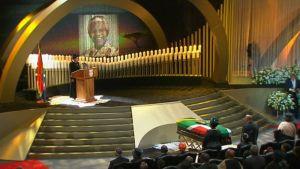 Hautajaispuhe. Mandelan arkku korokkeen edessä.