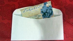 Kuvassa kirjekuoresta pilkistävä lahjakortti.