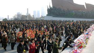 Pohjois-Korealaisia tuomassa kukkia Kim Jong-iliä esittävän patsaan luo.