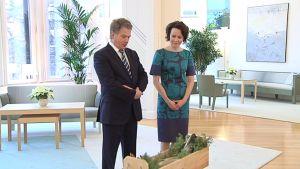 Presidentti Sauli Niinistö ja Jenni Haukio katselevat lahjaksi saamaansa jouluhaukea Mäntyniemessä.