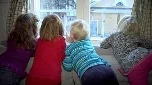 Lapsia päiväkodin ikkunassa.