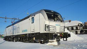 Valkoinen Siemens Vectron -veturi lumisessa maisemassa.