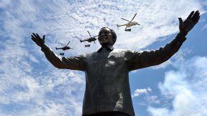 Helikopterit kantavat kansallislippuja, kun Nelson Mandelan yhdeksänmetrinen pronssipatsas paljastetaan Pretoriassa, Etelä-Afrikassa 16. joulukuuta 2013.
