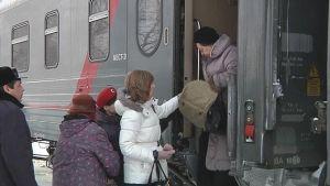 Venäläismatkailijat laskeutuvat junasta.