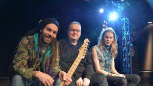 Turku Rock Academyn vastaava tuottaja Mark Bertenyi, toiminnanjohtaja Tomi Arvas ja Hangman's Voodoon rumpali Antti Yli-Halla akatemian esiintymislavalla Vimmassa.