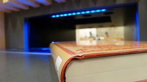 Kirjaston kirja menossa hihnaa pitkin palautusautomaattiin