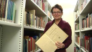 Kuvassa kirjastohyllyjen välissä seisova nainen pitelee avonaista kirjaa kädessään