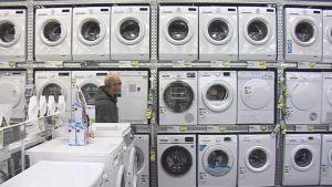Mies katsoo pesukoneita kaupassa.