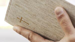 Mies lukee raamattua -lähikuvassa kädet.