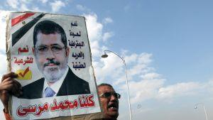 Mies pitelee Muhammed Mursiin kuvaa