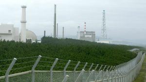 Ydinvoimala jonka edessä korkea aita.