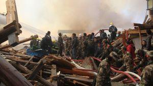 Sotilaita ja muita henkilöitä tulipalon raunioissa.