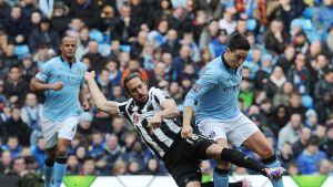 Newcastlen Jonás Gutiérrez (vas.) taklaa Manchester Cityn Samir Nasria (oik.).