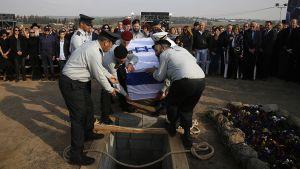 Israelin armeijan upseerit laskevat Ariel Sharonin arkun hautaan.