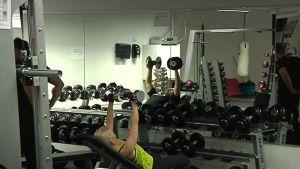 Nainen treenaa painoilla.