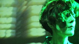Nainen laulaa vihreässä neonvaloissa.