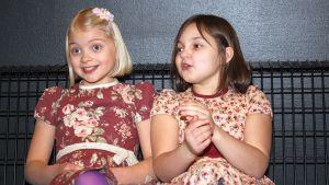 Onneli ja Anneli elokuvan tähdet Lilja Lehto ja Aava Merikanto istuvat elokuvateatterin aulassa.
