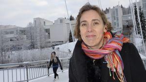 Tutkija Marja Tiirola yliopistorakennusten edessä.