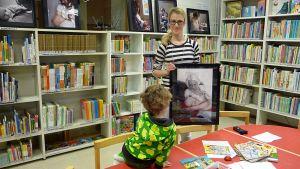 Sanna-Mari Prusila ja Noa-poika Keminmaan kirjaston lastenosastolla