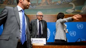 Lakhdar Brahimi seisoo keskellä pöydän takana. Etualalla nuori mies ja pöydän takana tummahiuksinen nainen viittoloi medialle.