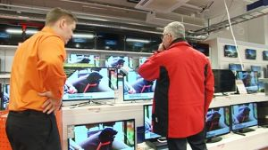 Myyjä ja asiakas katselevat televisioita elektroniikkakaupassa.