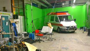 Vihreän kankaan edessä ambulanssi ja kuvaustekniikkaa.
