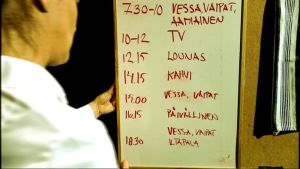 Hoitaja etualalla pitelee taulua, johon on kirjoittettu päivän aikataulu (vessa, vaipat ja aamiainen, TV, lounas, kahvi, vessa ja vaipat, päivällinen, vessa, vaipat ja iltapala).