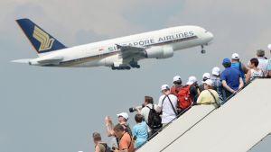 Ihmiset katselevat lentokoneen lähtöä