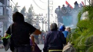 Väkijoukko heittelee esineitä sotilaita kohden.