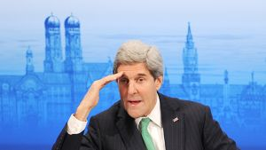 John Kerry on kohottanut kätensä kuin katsoakseen horisonttiin. Kerryn takana on sininen, historiallissävytteinen taustafondi, jossa on kaupunkimaisema torneineen.