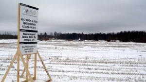 Rakentamisen aloittamisesta kertova teline seisoo pellolla Joensuun Multimäessä.