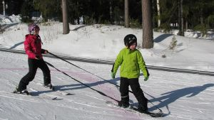 Liikuntarajoitteinen lapsi lumilautailee avustettuna Vuokatissa.