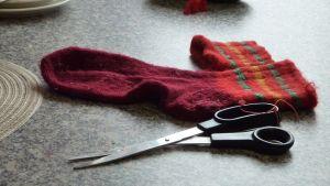 Hyrynsalmelaisnaisten ompeluseurassa villasukka ja sakset odottavat pöydällä.