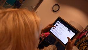 Nainen selaa verkkosivua tabletilla.