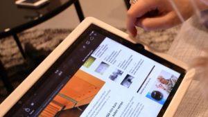 Nainen selaa tabletilla verkkosivuja niska kyyryssä.