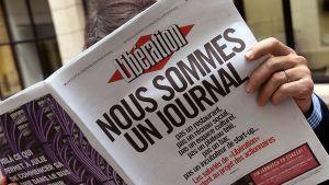 Mies lukee Libération-sanomalehteä.