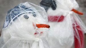 Muovilla suojattuja lumiukkoja vesisateessa.