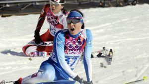 Aino-Kaisa Saarinen istuu maassa kilpailun maalissa.