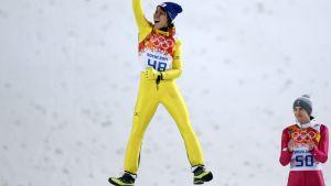Japanin Noriaki Kasai hyppää ilmaan palkintoseremoniassa. Puolan Kamil Stoch antaa aplodit.