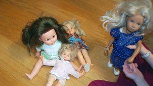 Kuvassa nukkeja lattialla ja tyttö leikkimässä niillä