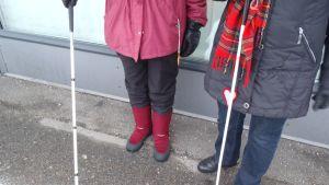 Näkövammaiset Raili ja Marianne valkoisine keppeineen.
