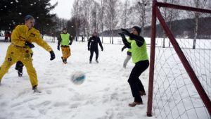 Opiskelijat pelaavat jalkapalloa hangessa.