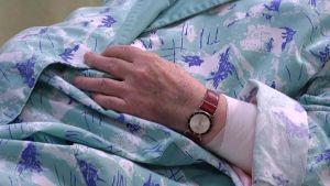 Sairaalassa olevan vanhuksen käsi, jossa on kello ja side.