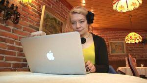 Katleena Kortesuo kannettavan tietokoneen ääressä