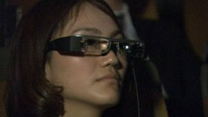 Nainen käyttämässä silmälaseja, joilla näkee oopperan sanat tekstitettyinä.