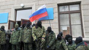 Naamioituneet miehet piirittävät hallintorakennusta Simferopolissa, Krimillä.