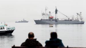 kaksi ihmistä katsoo venäläistä sotalaivaa