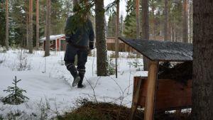 Mies kävelee pois eläinten ruokintapaikalta, jossa heinää.