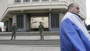 Venäjän lippuun kietoutunut mies on Krimin valtiopäivärakennuksen edustalla Simferopolissa 6. maaliskuuta. Taaempana on kaksi sotilasta vartiossa.